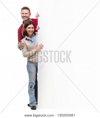 couple  peek out from behind empty blank isolated on white background