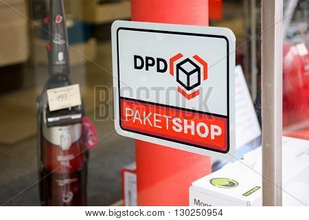 BADEN-BADEN GERMANY - NOV 20 2014: DPD Paket Shop logo on the entrance of a shop offering pick-up service for online orders. DPD is an international parcel delivery company owned by GeoPost La Poste France