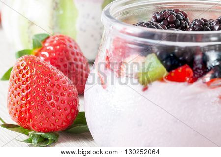 Closeup of jar with berries yogurt and ripe strawberries.