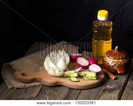 The cut vegetables on an old wooden table. Rural style close up dark background. A flower from a bulb radishes and a cucumber the cut with krudochka vegetable oil a knife