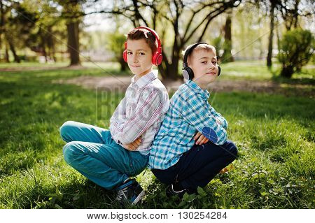 Two Brother Boy With Headphones Sitting On Park. Brother Love.