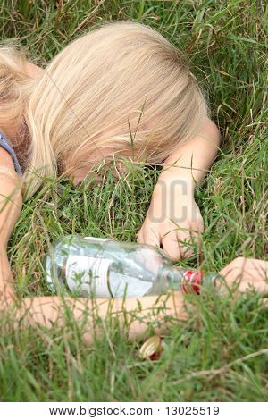 Teen alcohol addiction (drunk teen with vodka bottle)