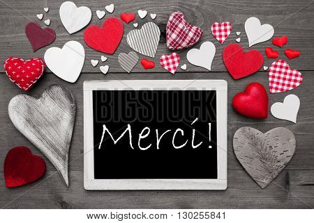 Chalkboard With French Text Merci Means Thank You. Many Red Textile Hearts. Grey Wooden Background With Vintage, Rustic Or Retro Style. Black And White Style With Colored Hot Spots
