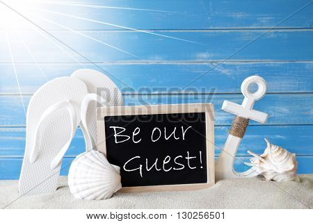 Chalkboard With English Text Be Our Guest. Blue Wooden Background. Sunny Summer Card With Holiday Greetings. Beach Vacation Symbolized By Sand, Flip Flops, Anchor And Shell.