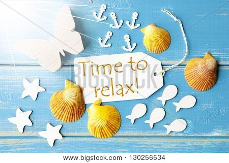 Flat Lay View Of Label With English Text Time To Relax. Sunny Summer Greeting Card. Butterfly, Shells And Fishes On Blue Wooden Background