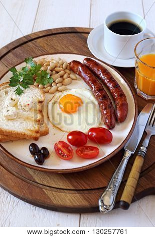 English breakfast with sausage fried egg baked beans and coffee