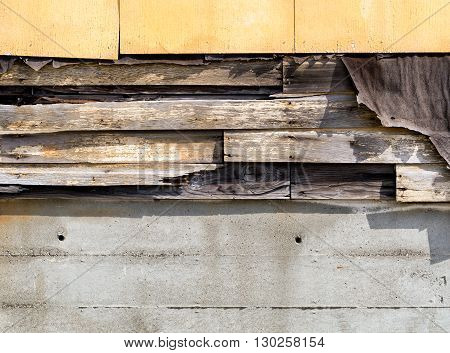 Asbestos siding falling apart with exposed wood and felt underneath.