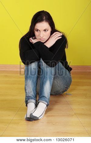 A worried and afraid young woman sitting on the flor.