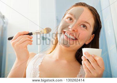 Woman Applying Mud Facial Mask