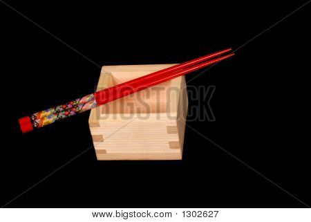 Wooden Sake Cup With Chopsticks Resting On Top On Black Backgrou