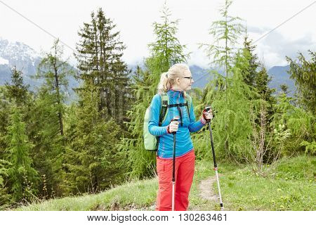 Blonde woman with ponytail wearing glasses and outdoor clothing and backpack, standing with trekking poles in hands during hiking track in Bavarian Alps - healthy lifestyle concept