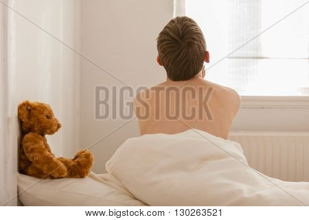 Back Of Boy Sitting Up From Bed Near Window