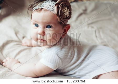 Portrait of a 4 month cute baby girl wearing lace flower headband and lying down on a bed