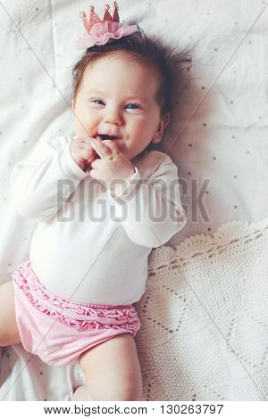 Portrait of a 4 month cute baby girl wearing princess crown headband and lying down on a bed with polka dot white bedding, top view