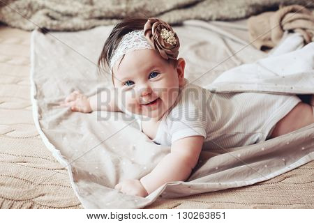 Portrait of a 4 month cute baby girl wearing lace flower headband and lying down on a bed with brown bedding