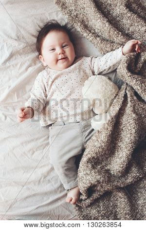 Portrait of a 4 month cute baby lying down on a bed with unrecognizable toy and soft blanket, top view