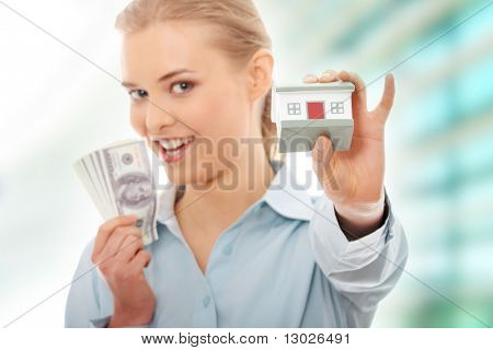 Portrait of beauty woman with money and toy house in hands