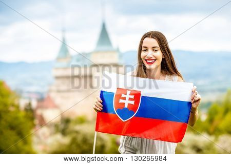 Young female tourist holding slovak flag with Bojnice castle on the background in Slovakia. Promoting tourism in Slovakia