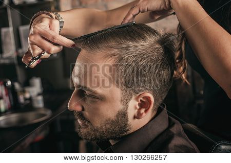 Skillful female hairdresser hairstyle hair of attractive man in hair salon