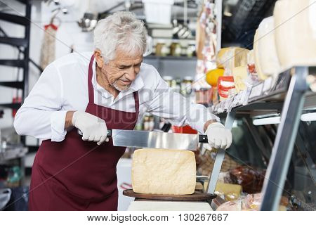 Salesman Slicing Cheese With Double Handled Knife In Shop