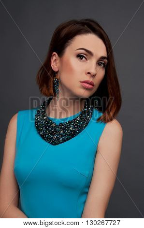 Sexy brunette in blue dress wearing beaded necklace and earrings