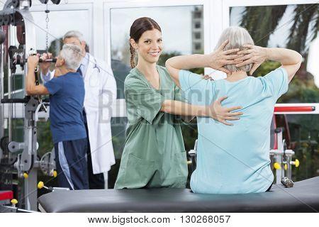 Female Nurse Assisting Senior Woman In Back Exercise