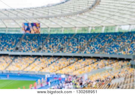 Blurred grand soccer arena or stadium with stands and spectators. 2016 sport background.
