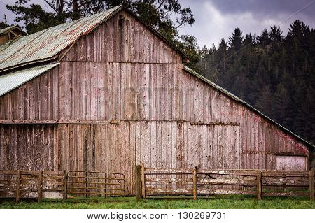An old barn on a rural farm with trees, sky and clouds.