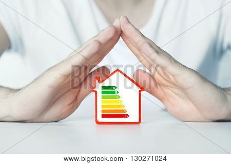Male hands over house with energy efficiency scale image