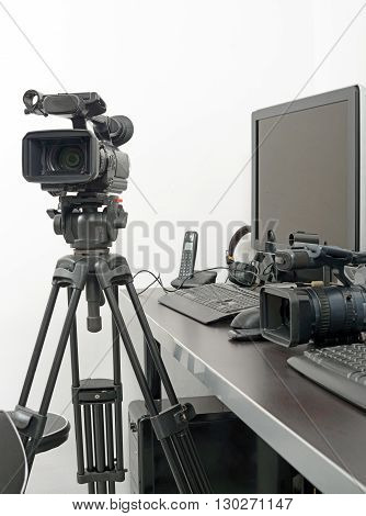 a professional video camera and computer for edition