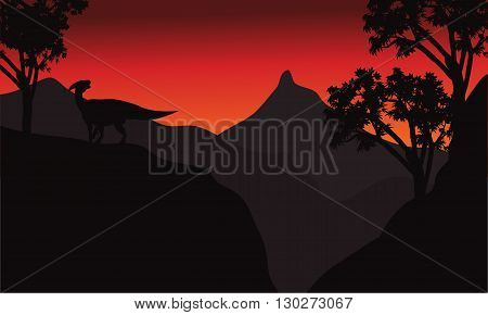 At sunset silhouette parasaurolophus in cliff scenery