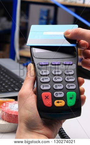 Hand of woman paying with contactless credit card with NFC technology in an electrical shop credit card reader payment terminal finance concept