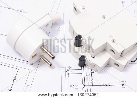 Electric plug and fuse lying on construction drawing of house accessories for engineering work energy concept