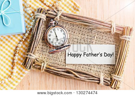 Happy father's day card paper with pocket watch and gift box on table.