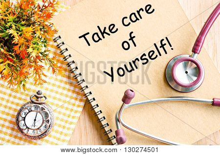 Take care of yourself on diary book and stethoscope with pocket watch on table.