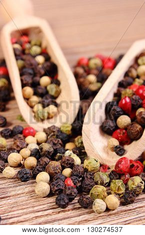 Heap of fresh colored pepper with wooden spoon lying on wooden table seasoning for cooking concept for healthy nutrition