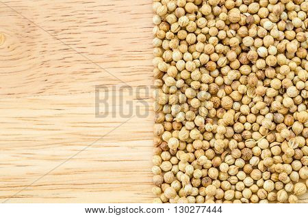 coriander seeds on wood background with copyspace.