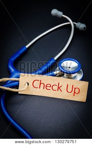 Check up word in paper tag with stethoscope on black background - health concept. Medical conceptual