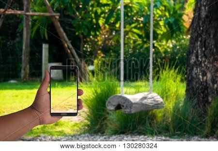hand of man hold mobile phone over blurred log swing hanging under the tree in garden