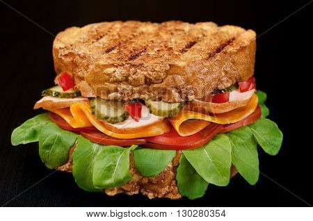 Big sandwich with ham, cheese, tomatoes, pickles and herbs. On a black background.