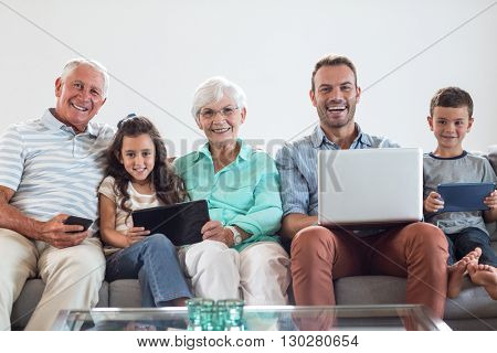 Happy family sitting on sofa using a laptop, digital, tablet, mobile phone in living room