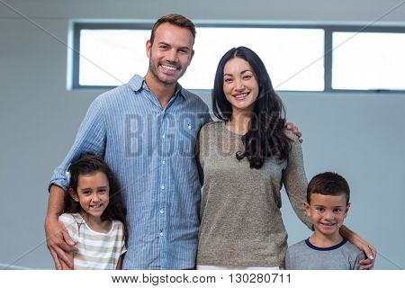 Portrait of family standing together and smiling in living room