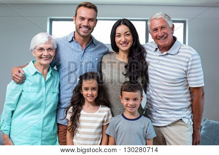 Portrait of happy family standing together and smiling in living room