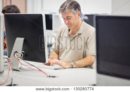 Professor working on computer in classroom