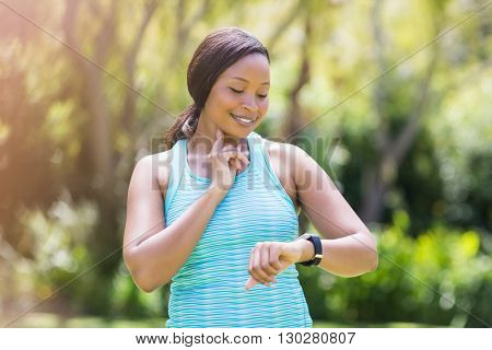 Happy woman posing and looking her watch
