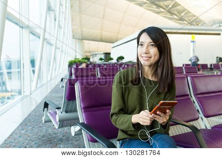Woman sitting down in waiting hall of airport