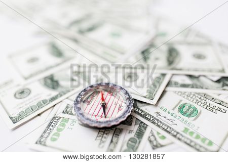 business, economy, finance and investment concept - close up of compass and dollar money