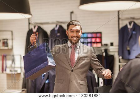 sale, fashion, retail, business style and people concept - happy man with shopping bags at clothing store