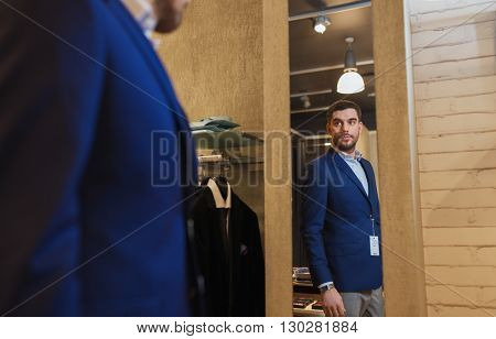 sale, shopping, fashion, style and people concept - young man choosing and trying jacket on and looking to mirror in mall or clothing store