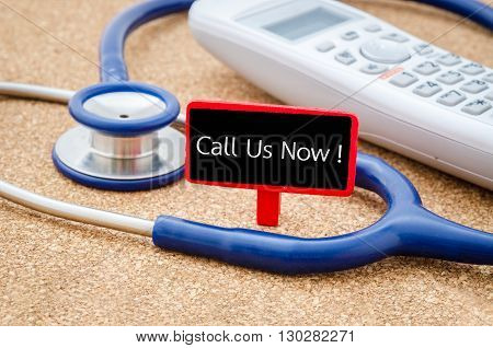 Phone and stethoscope on the table with Call Us Now words on the table. Medical concept.